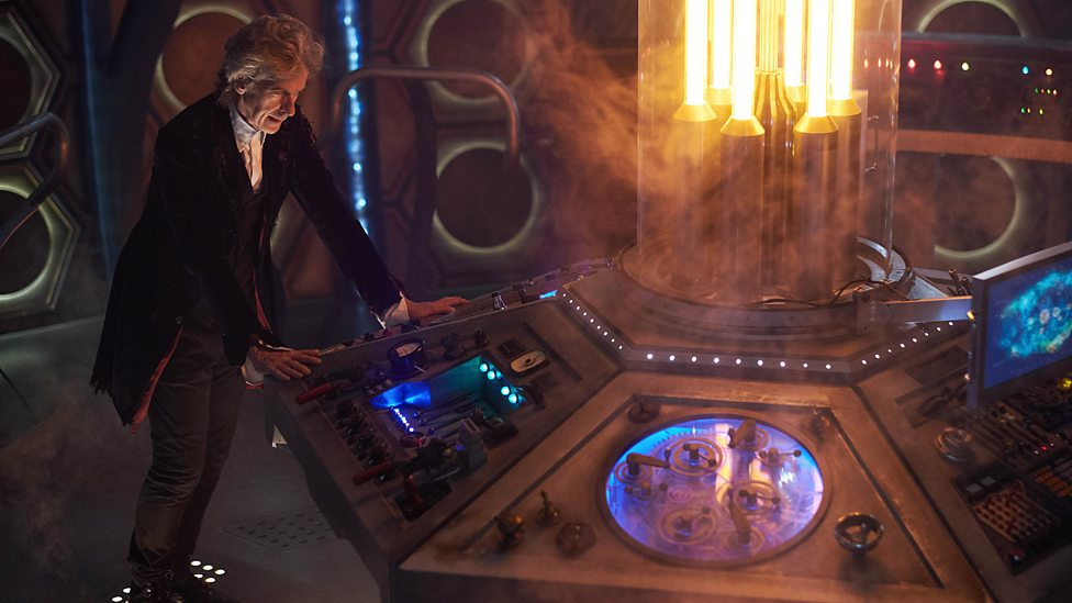 The Twelfth Doctor stands hunched over the TARDIS console